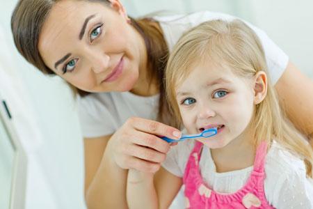 Mom and Daughter brushing their teeth - Pediatric Dentist in Duncan, SC and Spartanburg County